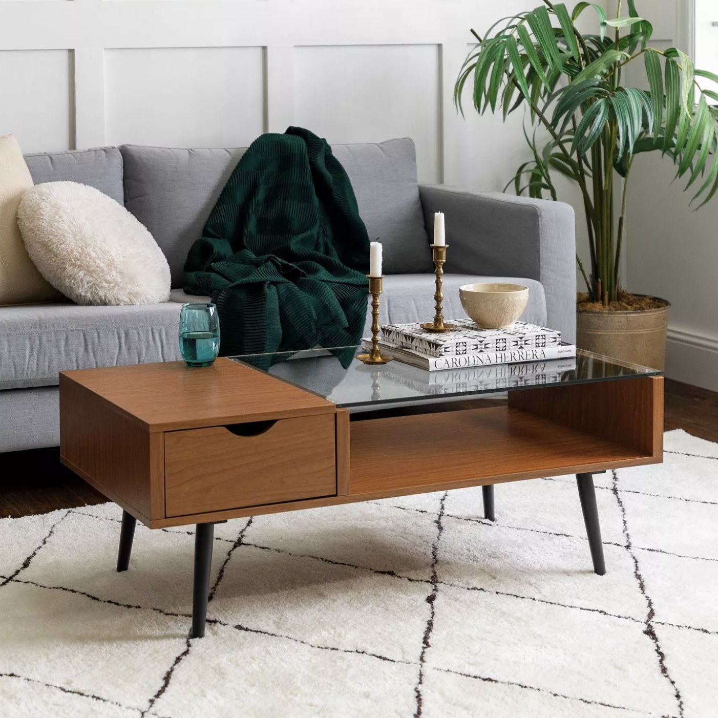 The glass and wood coffee table in front of a couch