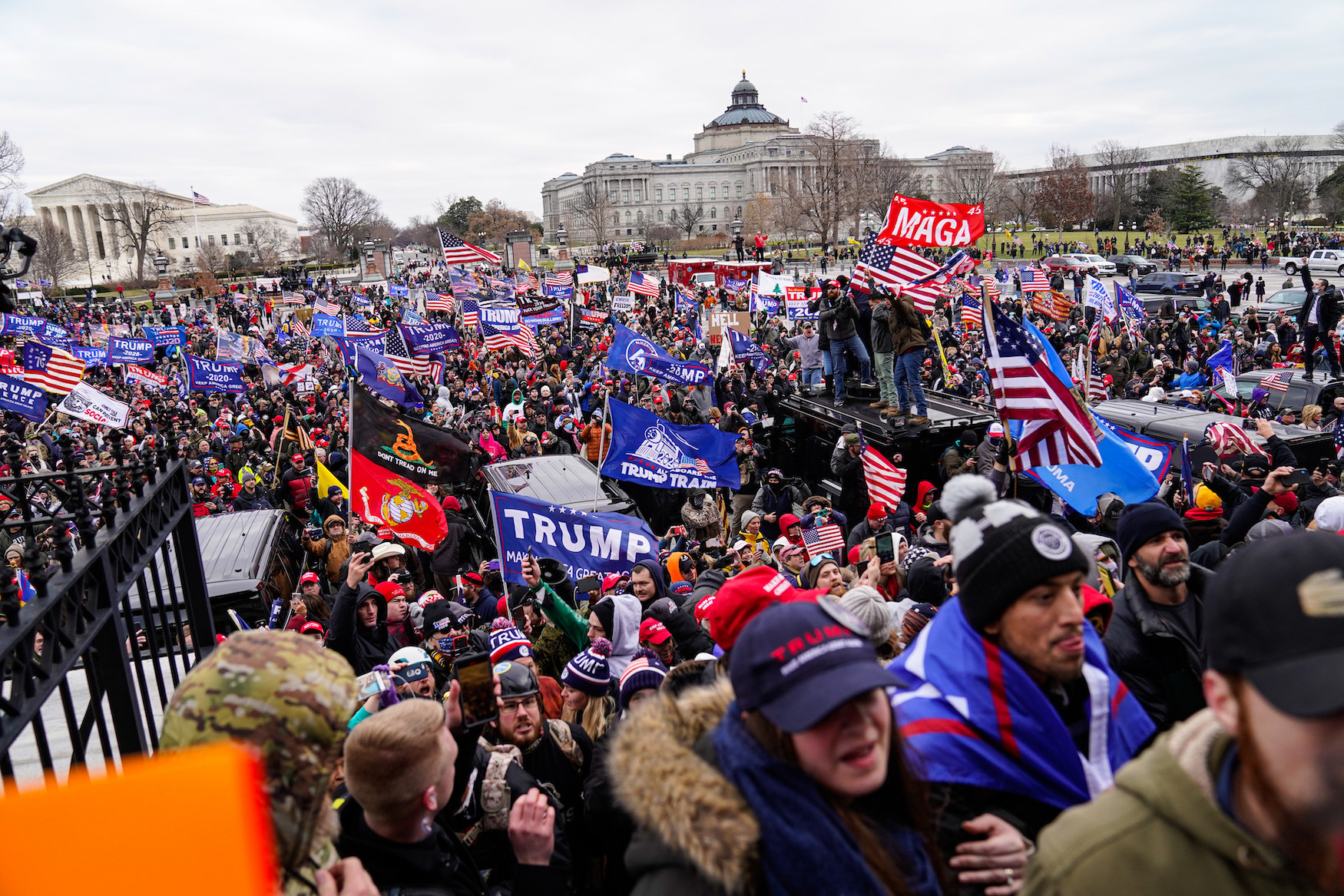 Crowds gather outside the U.S. Capitol carrying Trump and MAGA flags