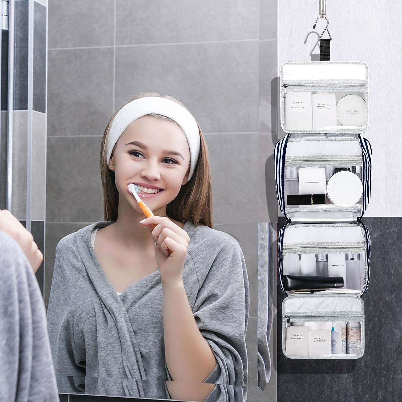 person brushing their teeth in the mirror with the hanging toiletry bag in the background