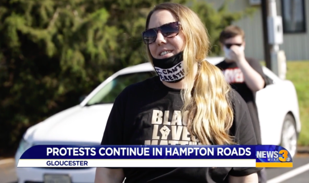 "A woman appears on a news program wearing a ""Black Lives Matter"" T-shirt and ""I can't breathe"" face mask"