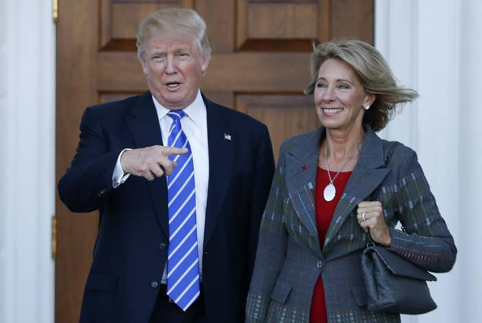 A smiling Trump points to a smiling DeVos as they stand together outside the White House on a sunny day