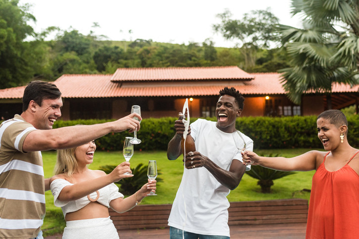 well-dressed teens popping champagne in front of a house