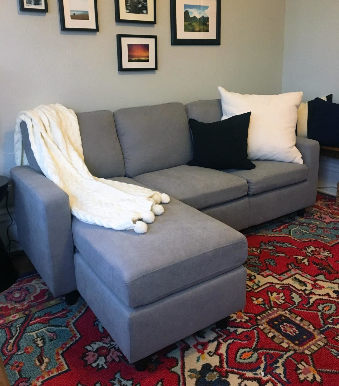 A reviewer's photo of the grey couch with the ottoman placed on the right