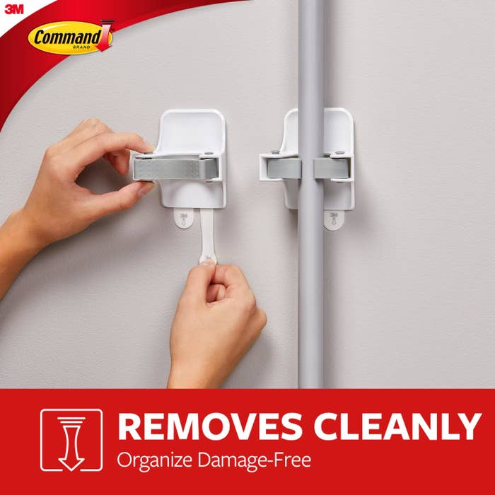 Two grippers, one holding a pole and the other being removed cleanly with text on the image saying removal won't damage walls