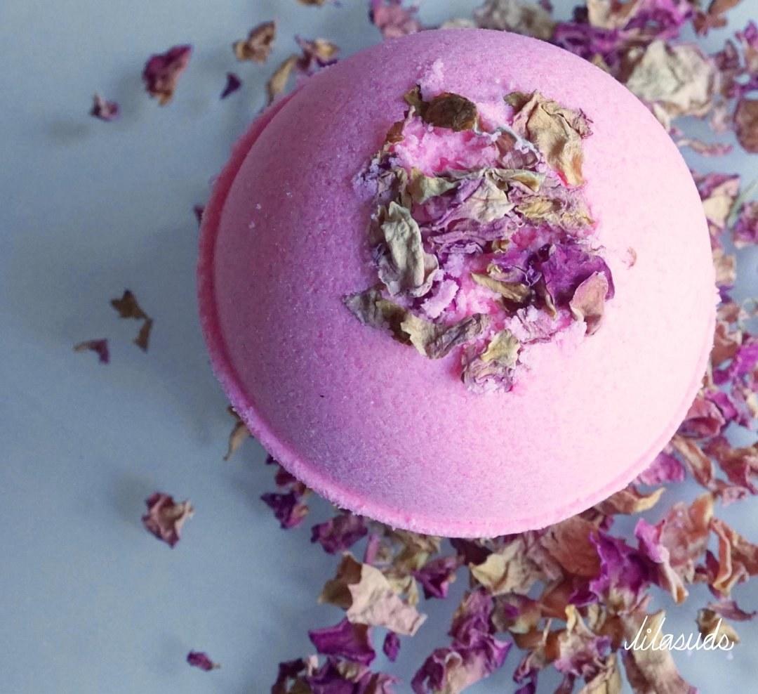 a pink bath bomb with potpourri around it
