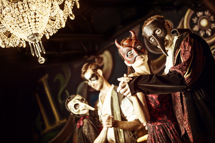 two couples dancing at a masquerade ball with masks and a chandelier above them