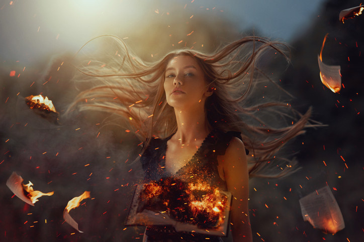 a woman with hair flying and burning books flying in the air around her