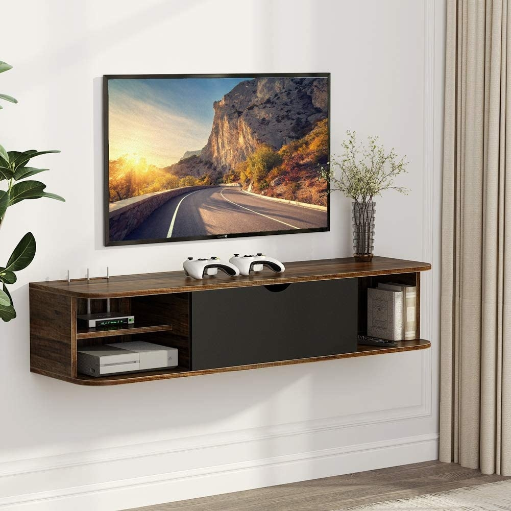 The vintage brown console which has three open shelves and a closed center compartment