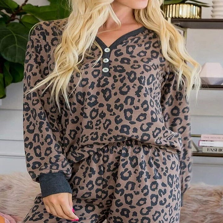 a model wearing a brown and gray leopard pajama top and matching bottoms
