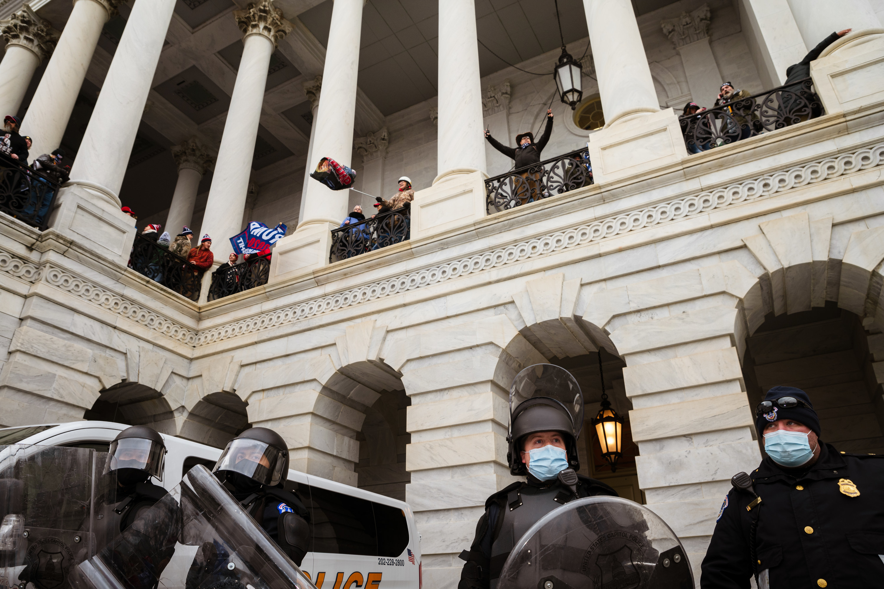 Trump supporters wave flags between columns at the Capitol building on a second floor; below them, police wear face masks, helmets, and shields