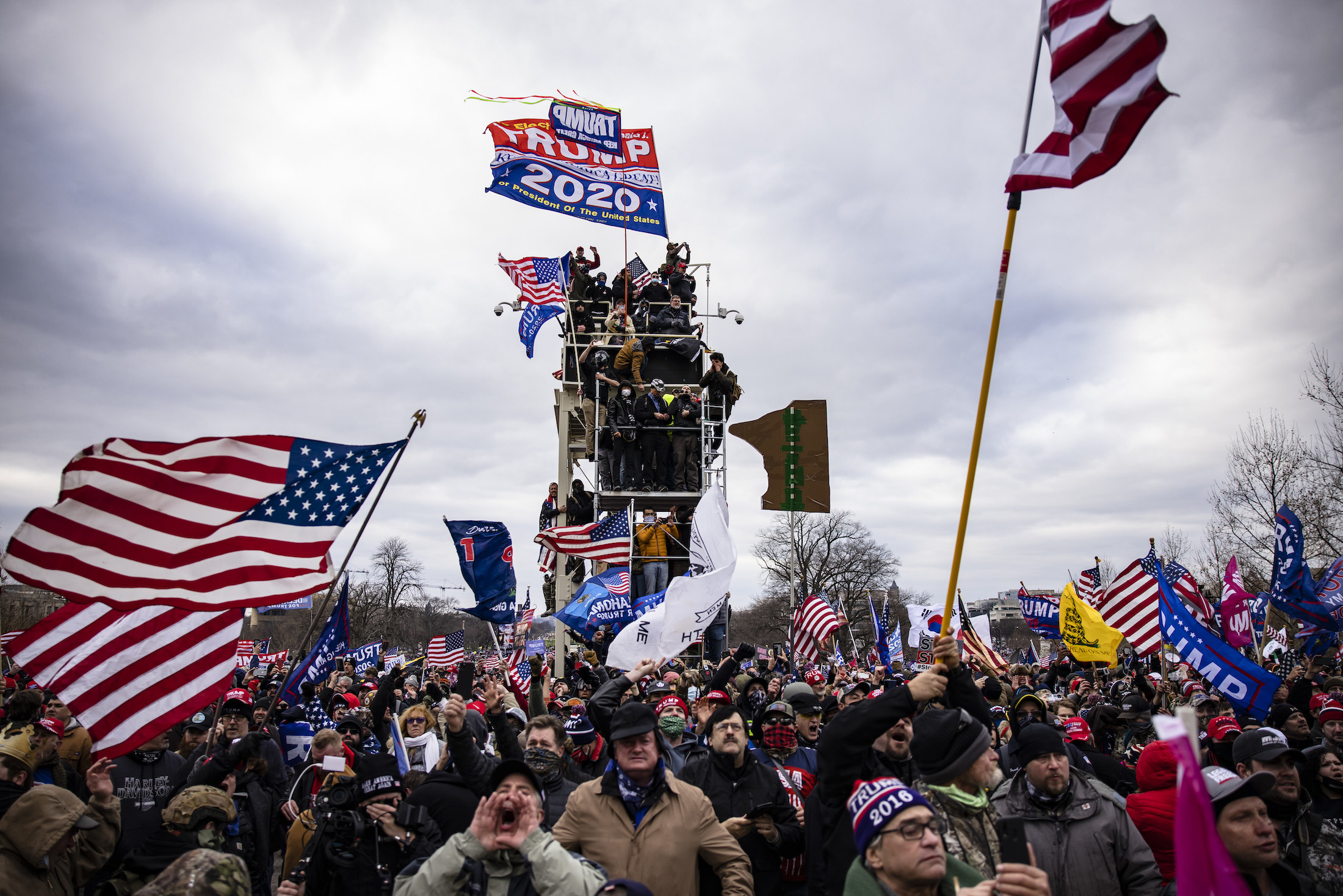 Pro-Trump supporters stand on a piece of scaffolding and wave Trump flags