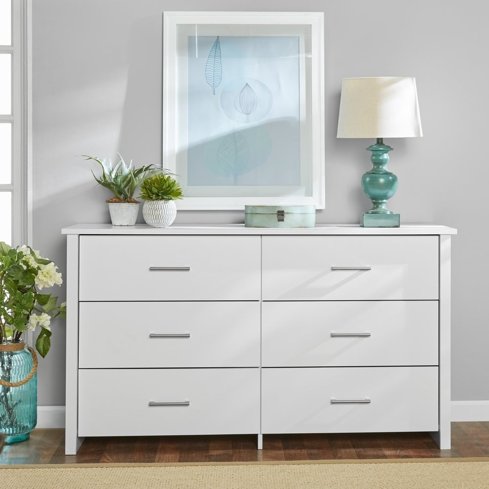 a white dresser with six drawers and silver hardware in a bedroom