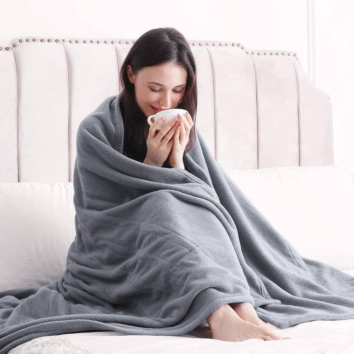 person wrapped in blanket holding a mug