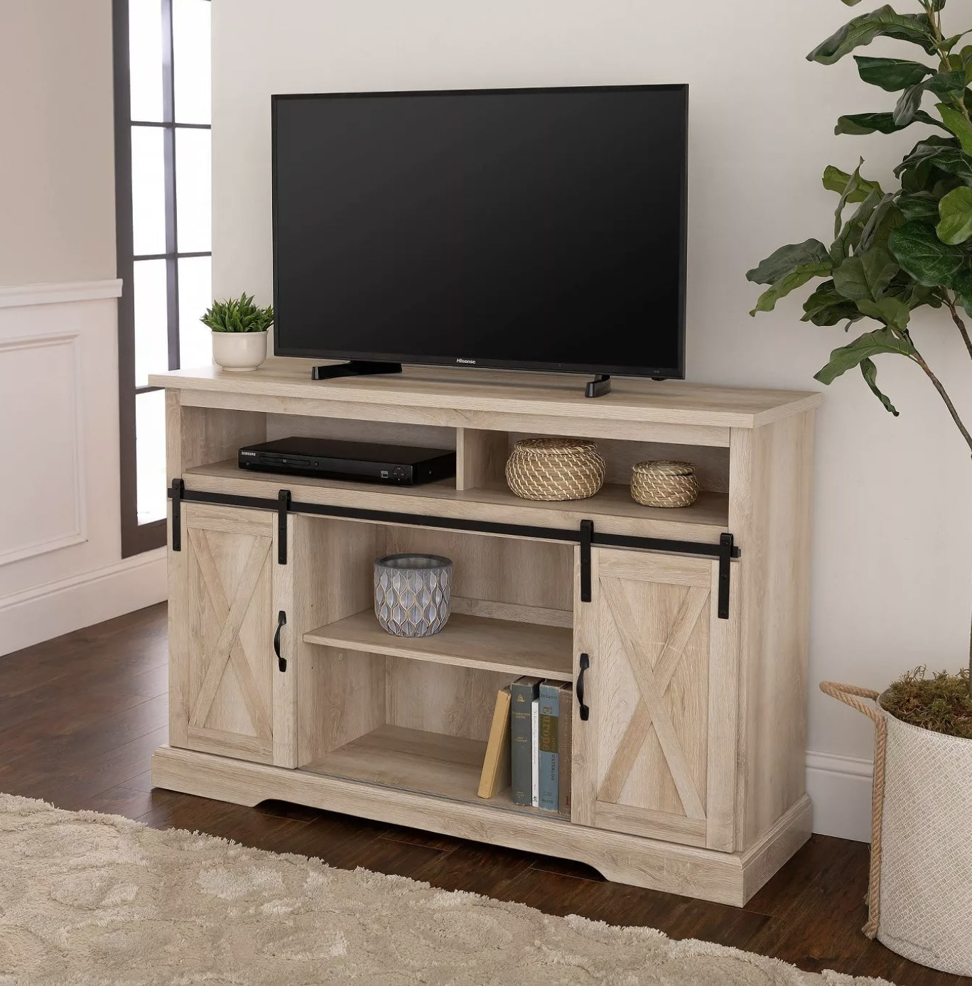 the TV stand in white oak with a tv, trinkets, and a DVD player shown on it