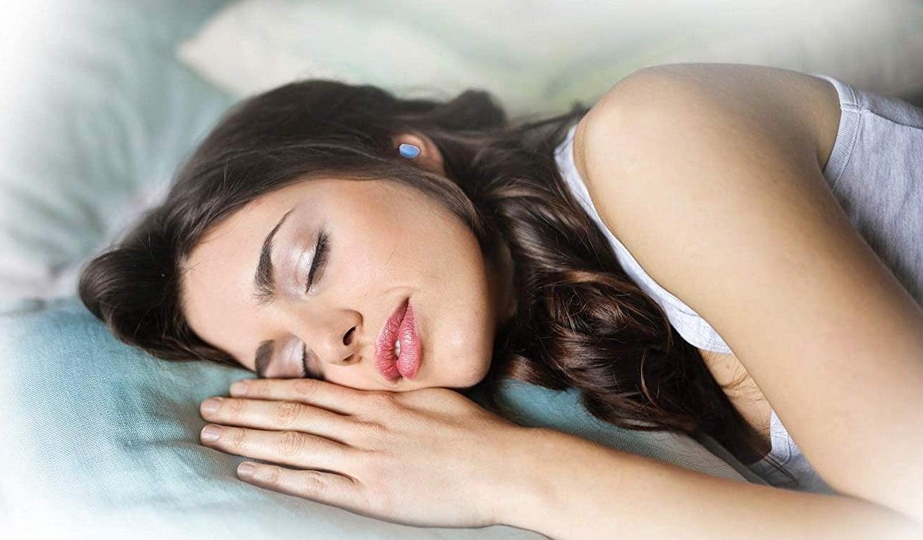 person sleeping with earplugs in