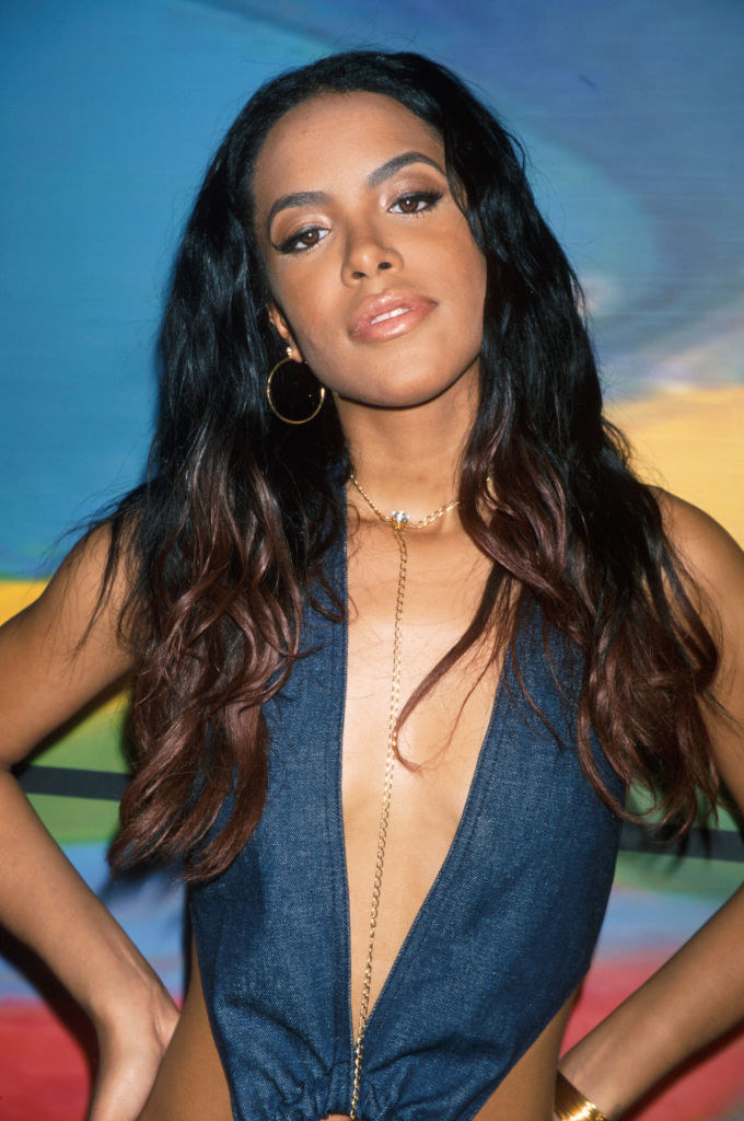 Aaliyah with long hair in front of a colorful background