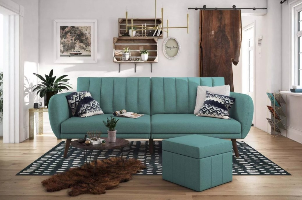 A teal sofa that converts to a bed
