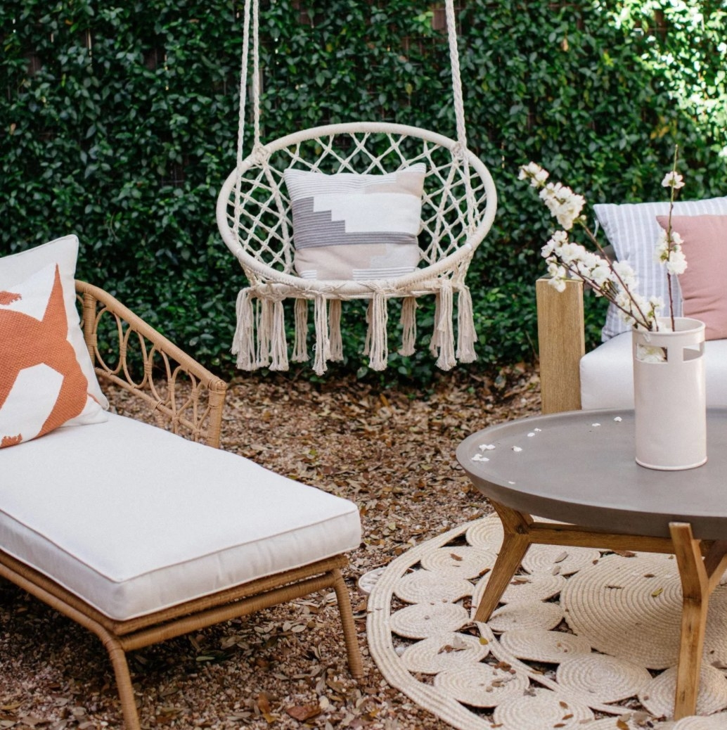 A white macrame hanging chair in a patio setting
