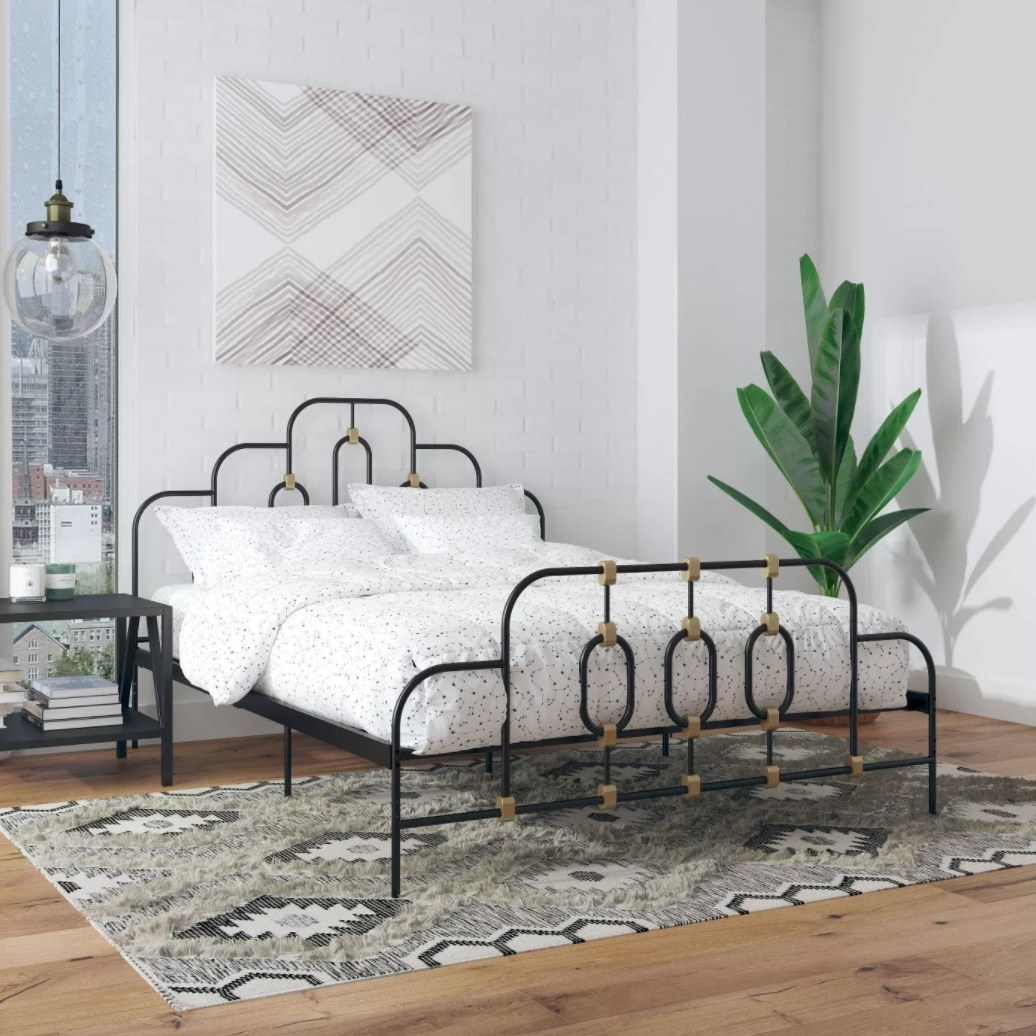 A metal bed frame with brass accent