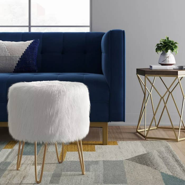A white faux fur ottoman with gold hairpin legs
