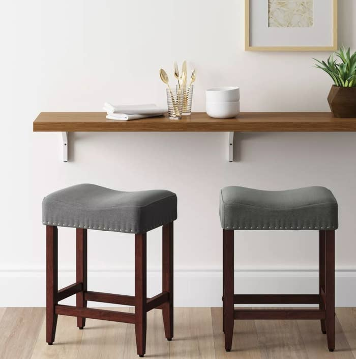 A pair of bar stools with gray cushions, nailhead detail, and wooden legs