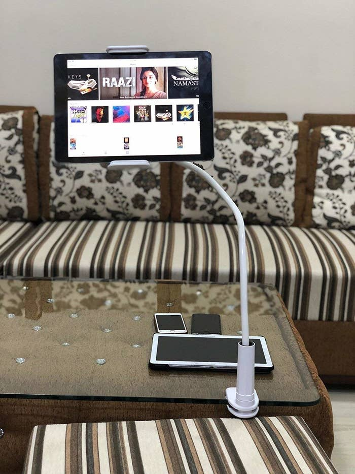A tablet clipped to the end of a table on the phone holder