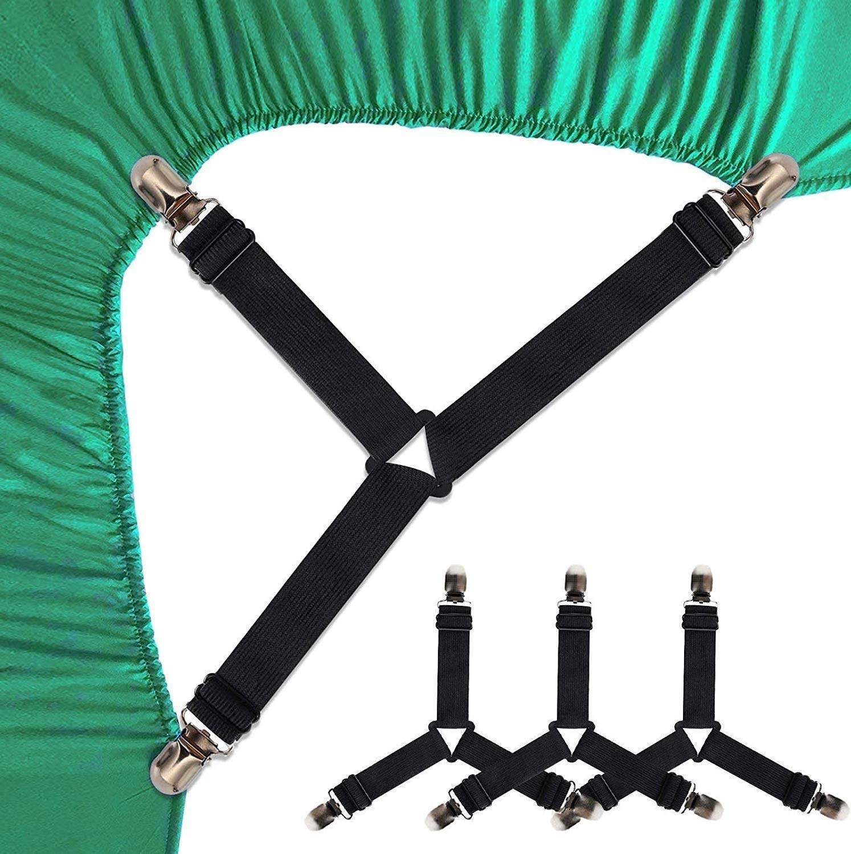 A set of black sheet suspenders on a green bedsheet