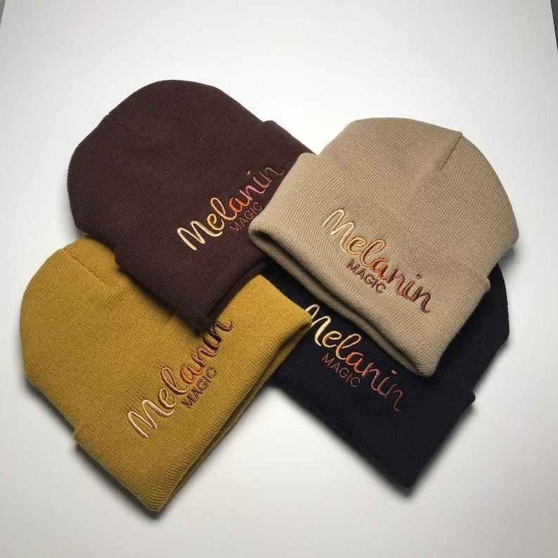 """five beanies that say """"Melanin Magic"""" on the front. they're in different colors like black, yellow, beige,and brown"""