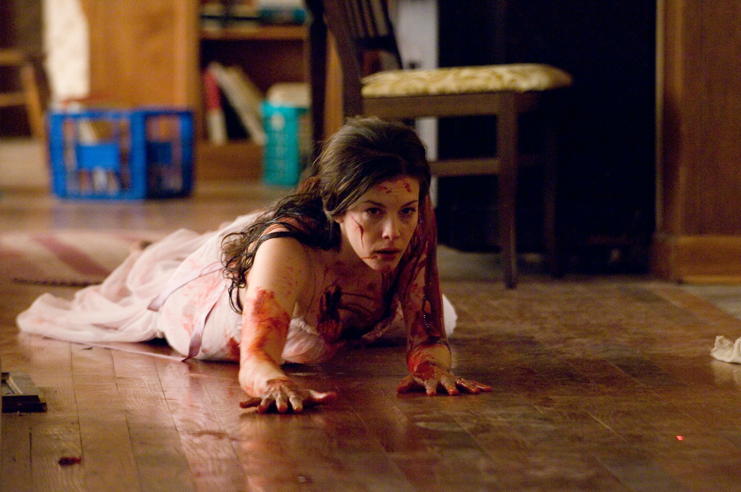Liv Tyler in the Strangers bloody and in distress on the floor as she tries to escape a trio of murders