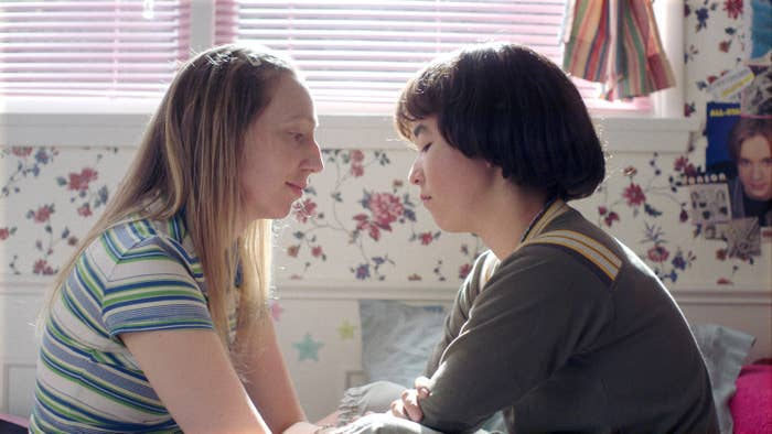 "Anna Konkle, wearing a green-and-white striped shirt, sits across from Maya Erskine, wearing a green shirt, in the PEN15 episode ""Sleepover"""