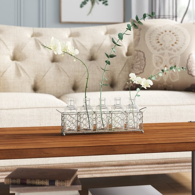 Distressed wire tray holds six glass bottles and white and green wildflowers on a brown table near a tan sofa