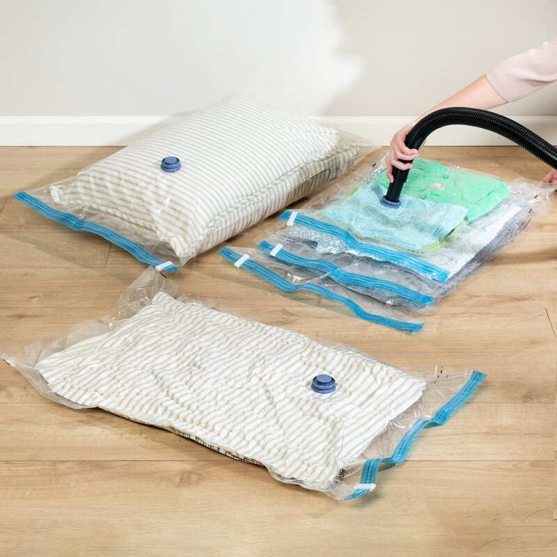 Model vacuums the air out of a clear storage bag with blue seal