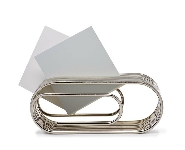 Stainless steel paper clip organizer holds pieces of white paper