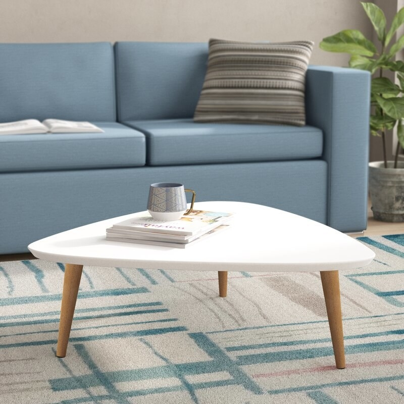 White triangular coffee table with brown legs and a gray and white mug on top sits on a cream, teal and pink rug beside a steel blue couch