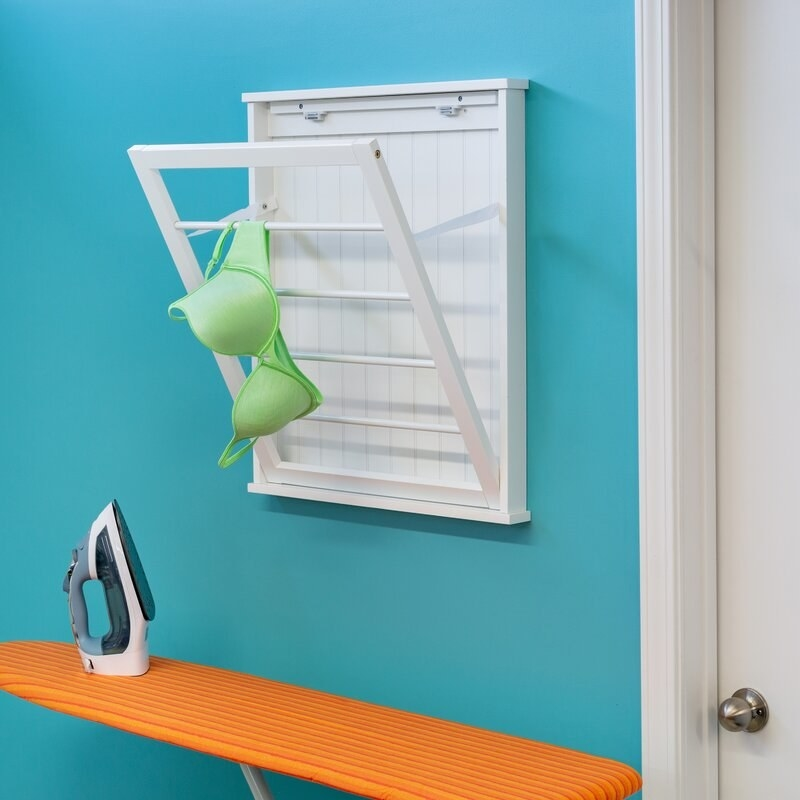 White drying rack on a teal wall holds a neon green bra over an orange ironing board