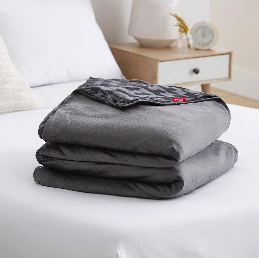 An Endy blanket folded up on a bed