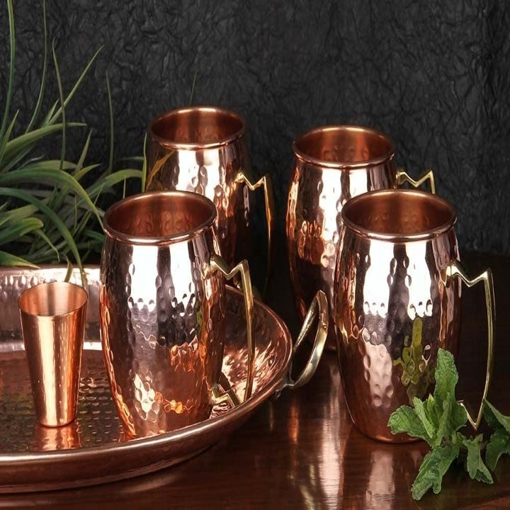 the four copper mugs with the copper shot glass next to them