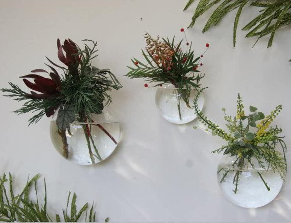 Three glass bulbs mounted on a wall filled with water and flowers