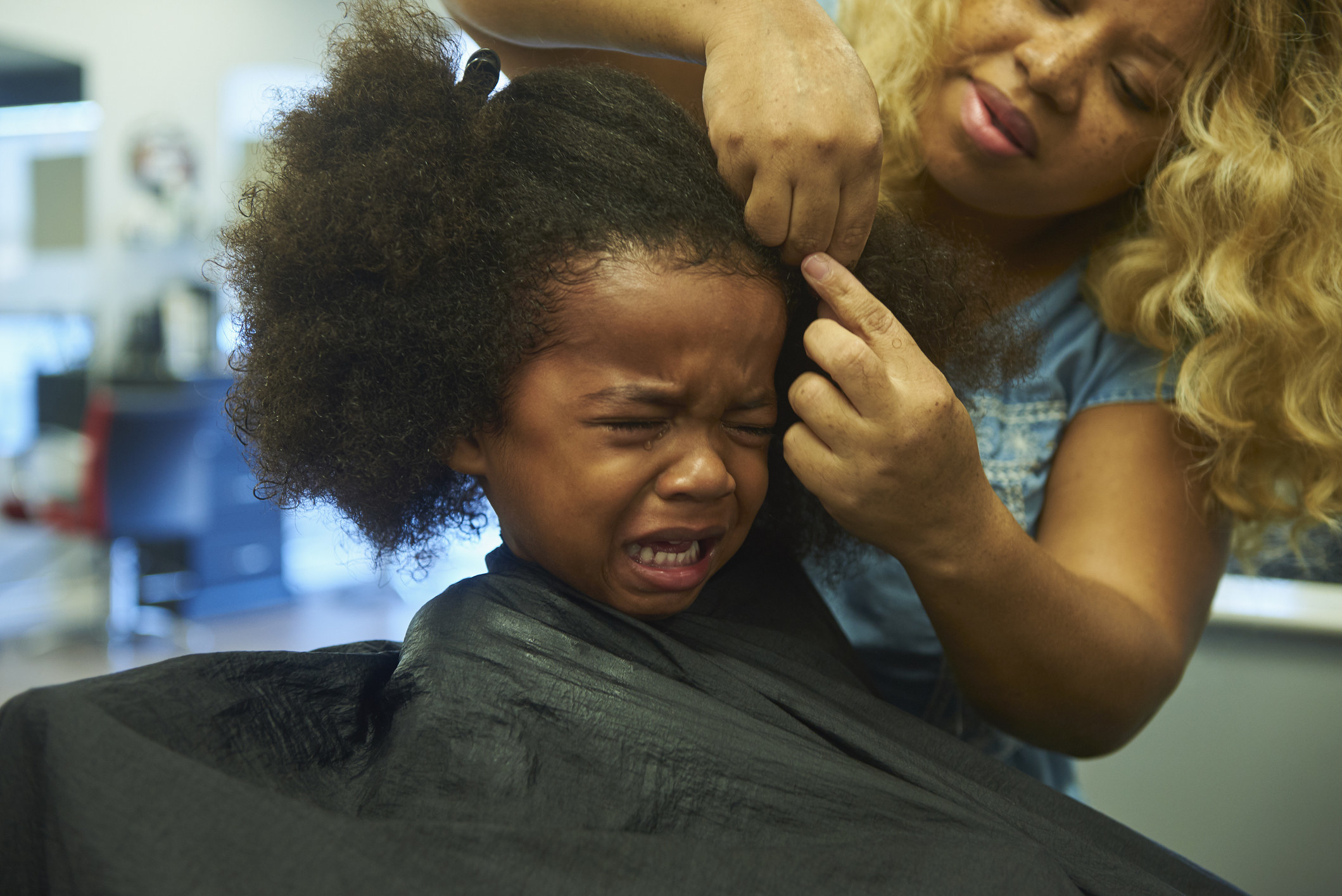 A child crying during their haircut