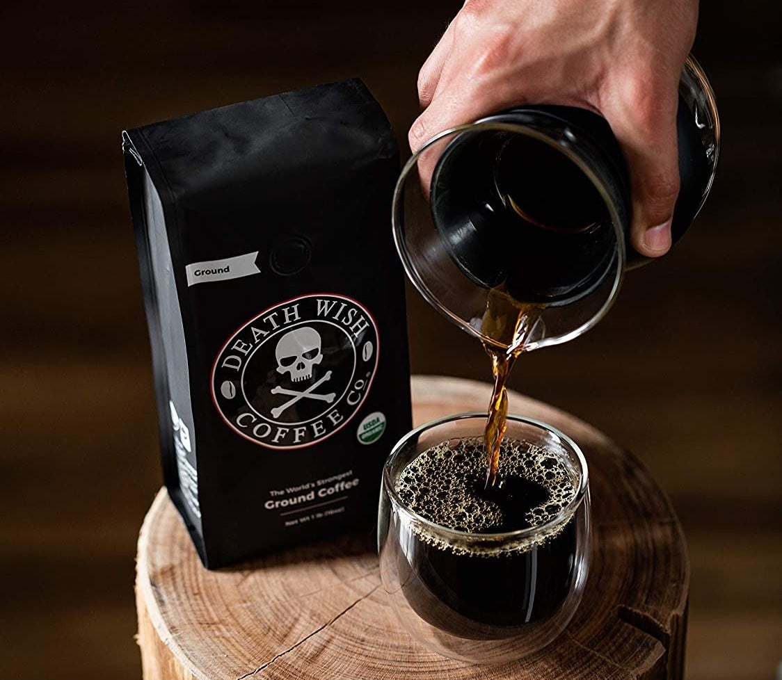 A model pouring black coffee into a clear cup next to a bag of Death Wish Coffee Co. Ground Coffee