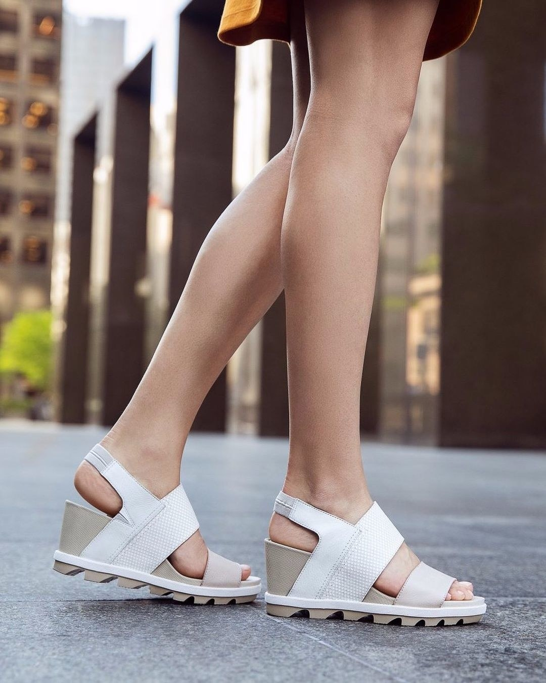 model wearing the open-toe wedge sandals with two white straps across the footbed, strap around the heel and grey wedge and sole
