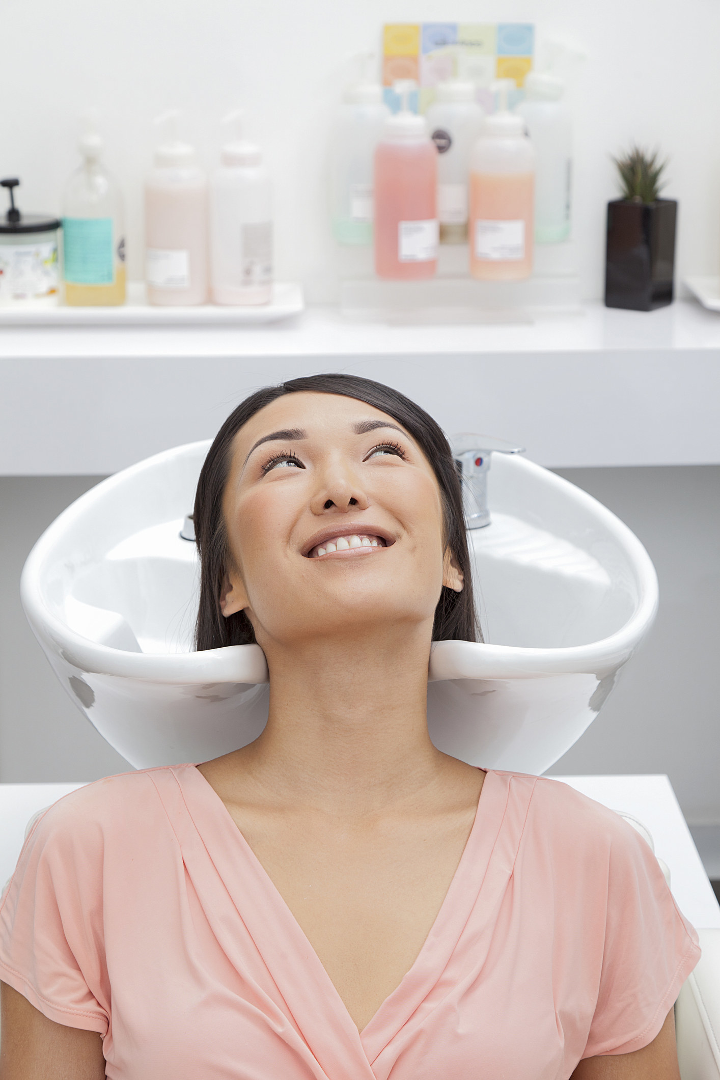 A woman receiving a shampoo at a salon