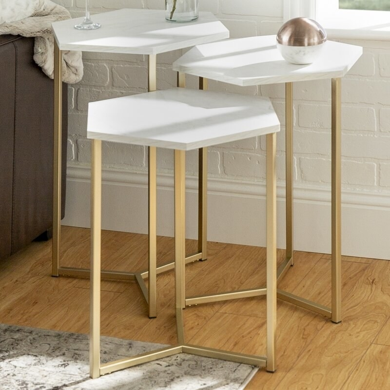 a set of three nesting tables with white hexagon tops and gold accent legs