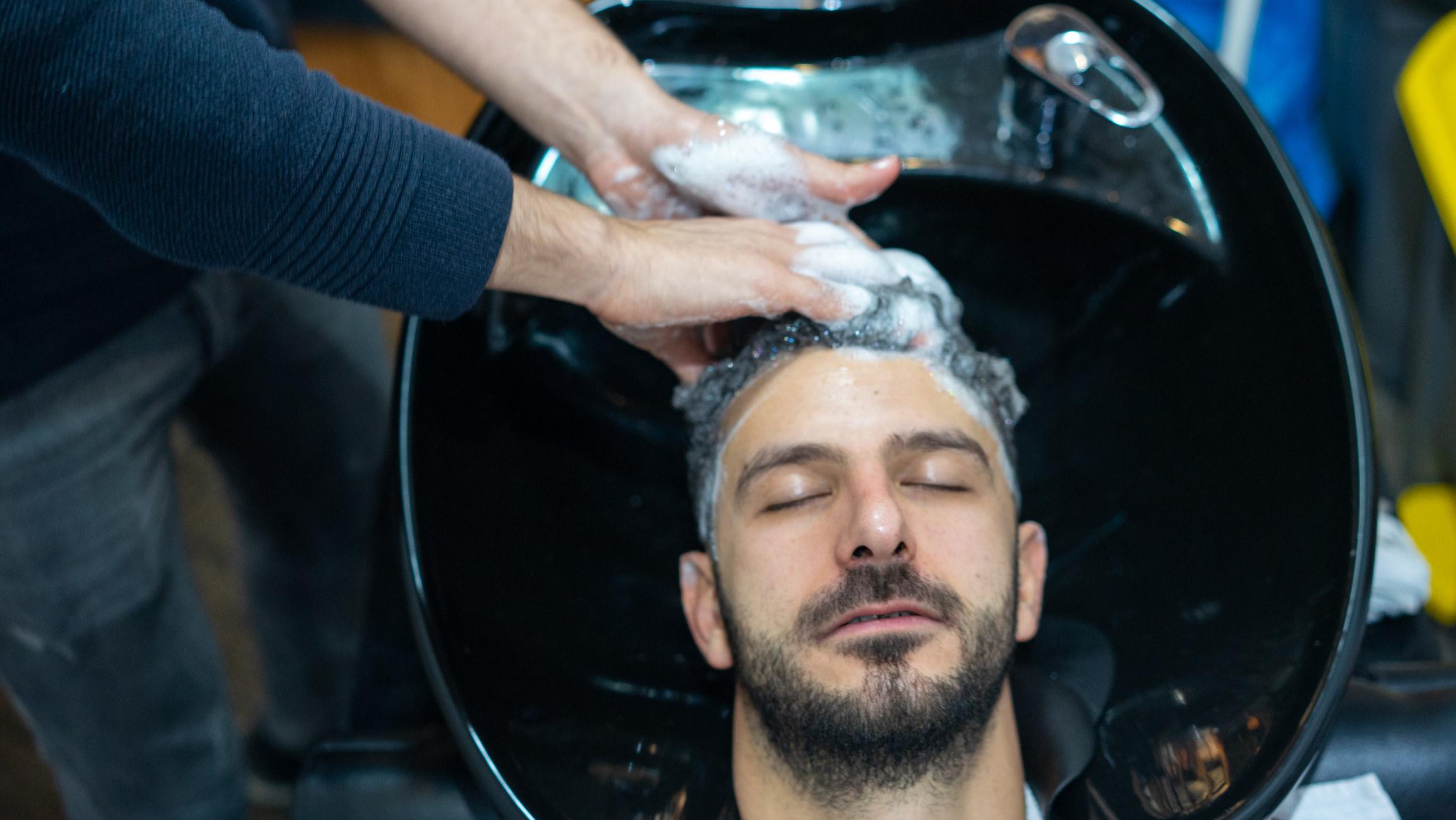 A man receiving a shampoo from a salon worker