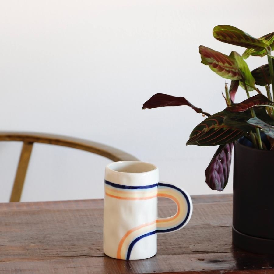 A tall white mug with a rainbow handle