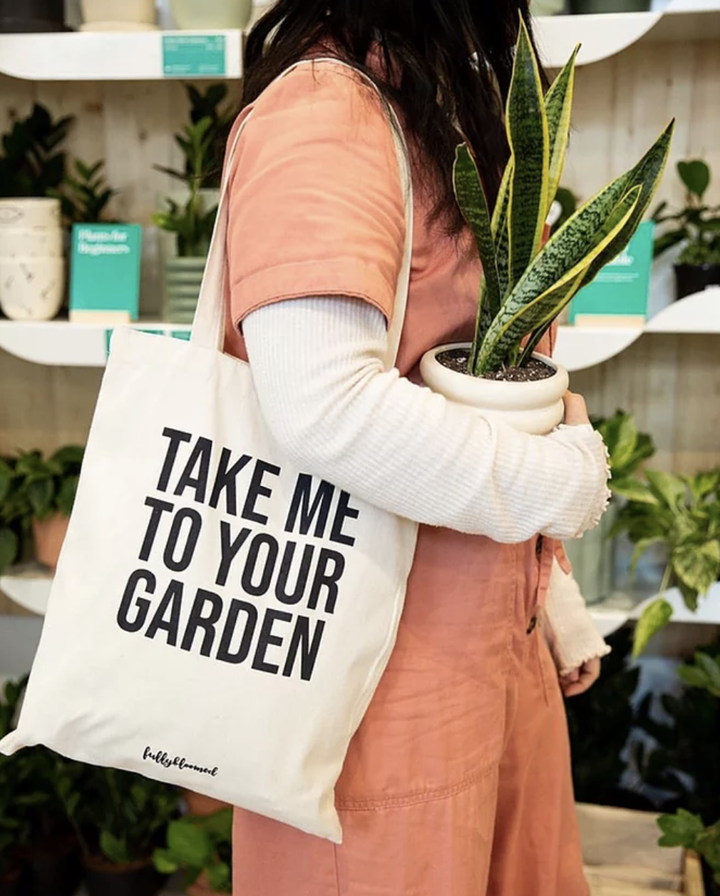 """a model wearing a tan tote bag that says """"take me to your garden"""""""
