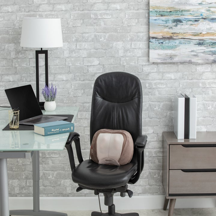 brown massage pillow on a black office chair