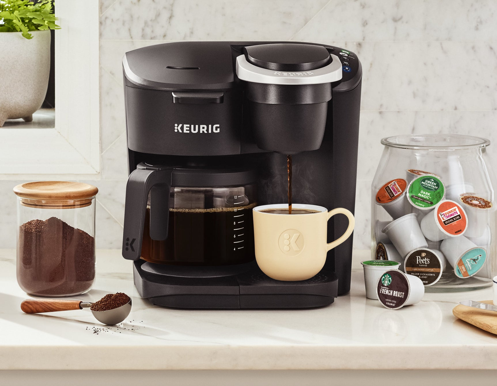 black keurig coffee machine with a pot on one side and a mug on the other