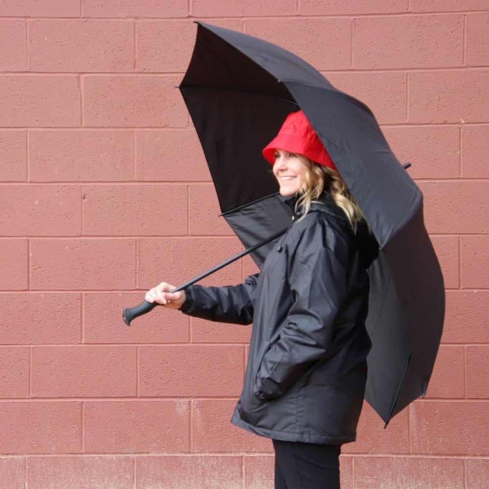a model standing under a black umbrella