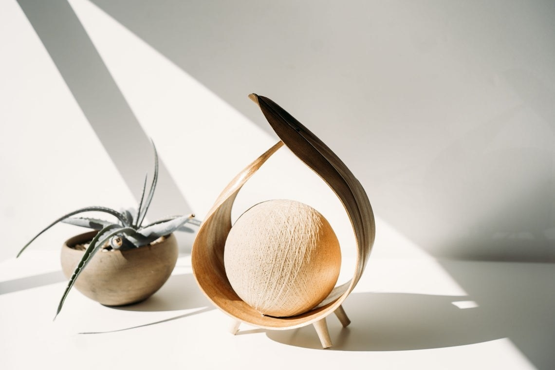 Seed-like lamp with glowing orb inside curved leaf design with three legs